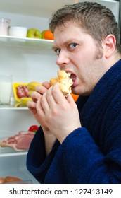 Handsome man eating piece of cake near open fridge
