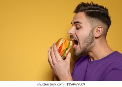 Handsome man eating tasty burger on color background. Space for text