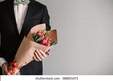 Handsome man in an elegant suit giving a bouquet of yellow tulips. Valentine's Day, Women's Day, Mother's Day. Wedding concept. Copy space.