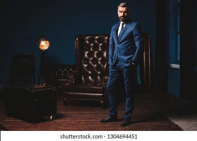 Handsome Man In Elegant Suit In Luxury Interior. Closeup Portrait Of Fashionable Confident Man In Luxurious Apartment