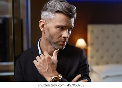 Handsome Man In Elegant Suit With Stylish Watch In Luxury Interior. Closeup Portrait Of Fashionable Confident Man In Luxurious Apartment