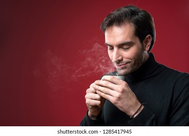 Handsome man enjoying the smell of his coffee or tea