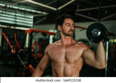 Handsome Man exercise in gym body-building with muscular strong body
