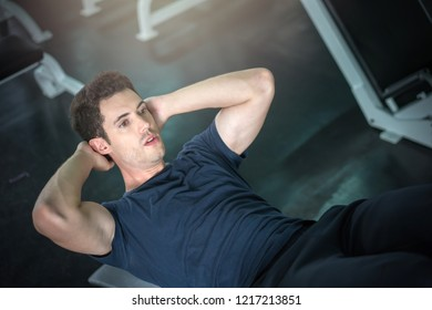 Handsome man exercising doing sit up abdominal exercise in gym.