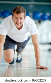 Handsome man exercising at the gym doing push ups