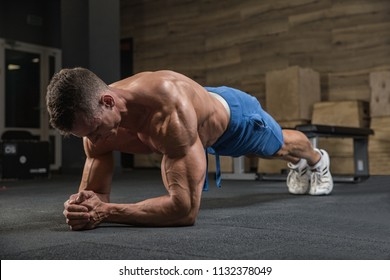 Handsome man is exercising in the gym, posing in front of the camera.