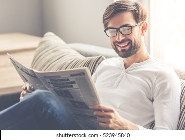 Handsome man in eyeglasses is reading a newspaper and smiling while sitting on couch at home