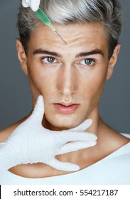 Handsome man face and beautician hands with syringe. Doctor makes cosmetic injection in forehead. Beauty concept