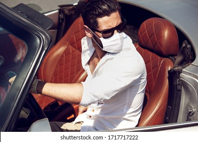 Handsome man in face mask in the car