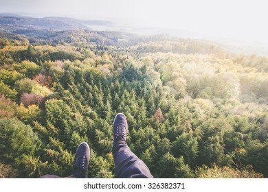 handsome man in fall clothes sitting on the edge of high tower above forest