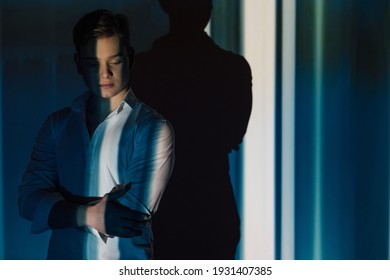 Handsome man. Fashion style. Model shooting. Success leadership. Confident guy in white shirt holding hands chest in dark shadow light interior silhouette reflection background copy space.