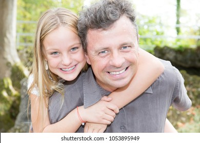 handsome man father piggyback blond beauty daughter in summer park
