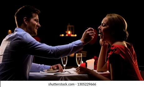 Handsome man feeding pretty lady, couple having romantic dinner at restaurant