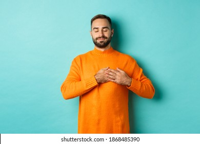 Handsome man feeling nostalgic, holding hands on heart and daydreaming, remember or imaging something, standing carefree against turquoise background