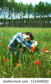 Handsome man in a field of green wheat and poppies
