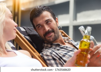 Handsome man flirting with a woman by inviting girl  cheers and clinking bottles glass of alcohol drink hangout together in a resort. Handsome guy enjoy drinking punch drink. Player man look at woman