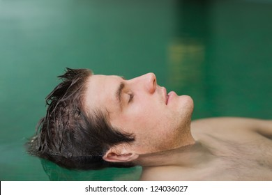 Handsome man floating in the swimming pool