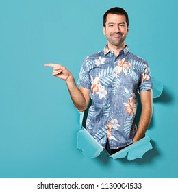Handsome man with flower shirt pointing to the lateral through a blue paper hole