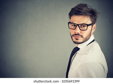 Handsome man in formal outfit and eyeglasses looking successful while standing on gray background.