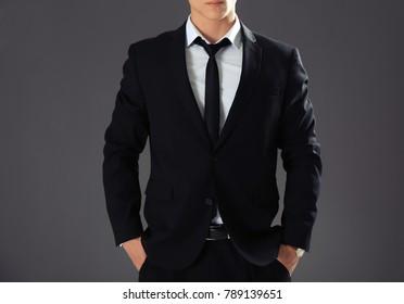 Handsome man in formal suit on grey background