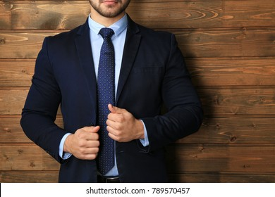 Handsome man in formal suit on wooden background, closeup
