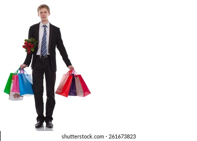 Handsome Man in full growth in a Business suit in Hands Holds Many Gift Bags and a Bouquet of Red Roses over a White Background