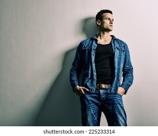 Handsome man - full jeans, thinking relies on the Wall
