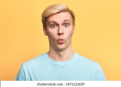 handsome man with funny facial expression learning to whistle., singing a song, flirting with a girl. close up photo. islated yellow background, emotion concept