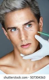 Handsome man gets beauty facial injections. Photo of an Attractive man gets Botox injection in eyes zone. Aesthetic Cosmetology concept