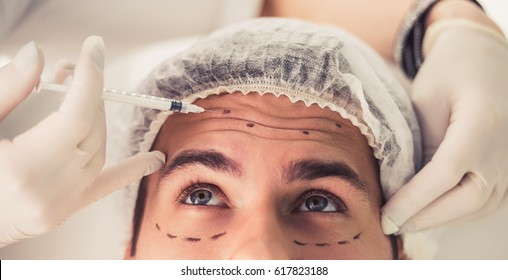 Handsome man is getting face skin treatment. Doctor in medical gloves is making an injection, close-up