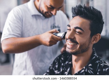 Handsome man is getting shaved by hairdresser at the barbershop