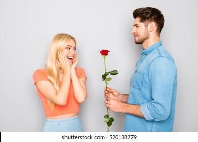 Handsome man giving red rose to his surprised girlfriend.