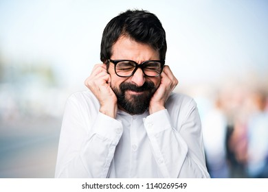 Handsome man with glasses covering his ears on unfocused background