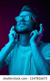 Handsome man in glasses enjoys listening to music with headphones. Neon studio portrait