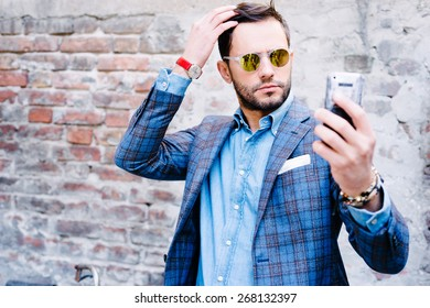 Handsome man with glasses ina suit, against old vintage wall, outdoors. taking a selfie
