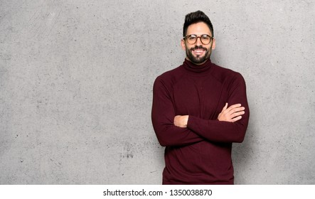 Handsome man with glasses keeping the arms crossed in frontal position over textured wall