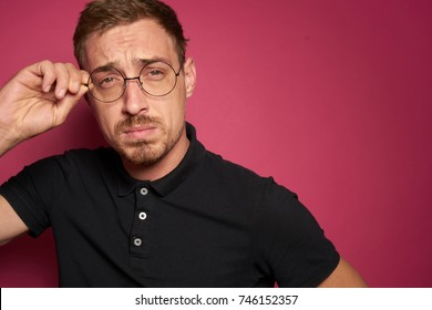 handsome man in glasses on a pink background, studio