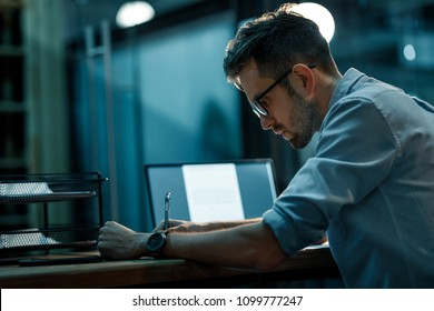 Handsome man in glasses and shirt writing in notepad sitting at desk with laptop in empty dark office.