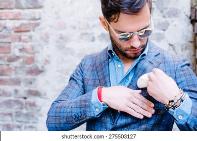 Handsome man with glasses in a suit, against old vintage wall, fixing his pocket square