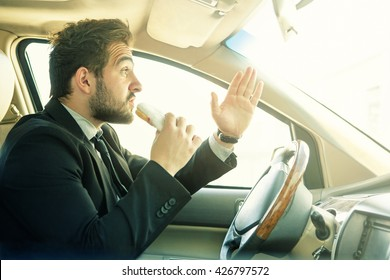 Handsome man going to eat hamburger. Bearded hipster in black suit having break. Close-up of delicious hamburger with beef.