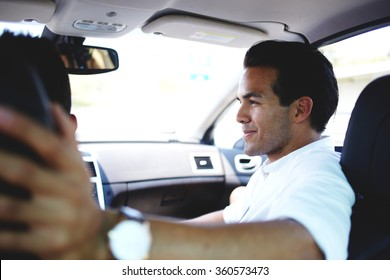 Handsome man in good mood talking with driver about their plans for the weekend while sitting on front seat in comfortable automobile, young male passenger enjoying road trip in car with his friend