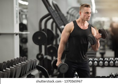 handsome man in good shape with muscles in the gym exercising exercises with dumbbells