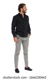 Handsome man in gray trousers, black shirt and moccasins is standing, holding hand in pocket and looking away. Full length studio shot isolated on white.