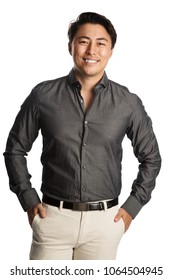 Handsome man in a grey shirt standing against a white background with a big smile on his face.