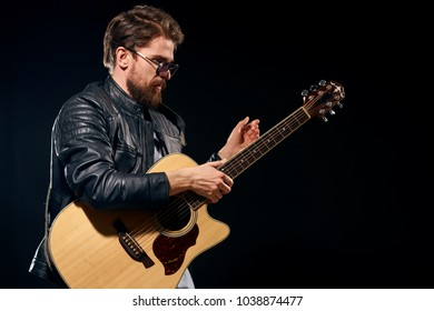 handsome man with a guitar on a dark background, group