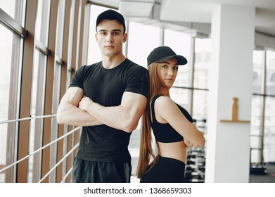 Handsome man in a gym. Sportsman in a sportswear. Couple training