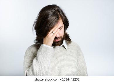 Handsome man has a headache, with long hair, isolated studio photo