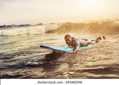Handsome man has surfing on small waves. Mixed race dark skin and beard. Summer sport activity