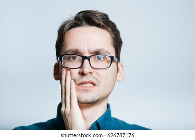 handsome man has a toothache isolated on a gray background