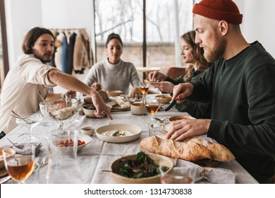Handsome man in hat with beard sitting at the table with baguettes thoughtfully looking aside. Group of young international friends spending time together on lunch in cozy cafe